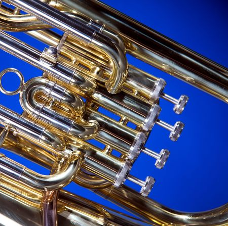 A gold brass tuba euphonium isolated against a blue background in the square format with copy space. photo