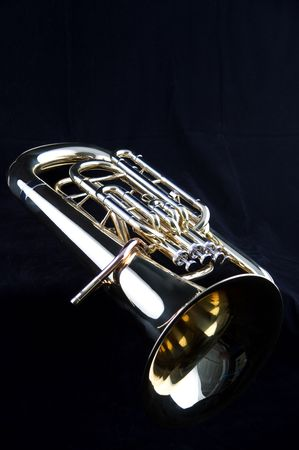 A gold brass bass tuba euphonium isolated on a black background in the vertical format with  copy space.