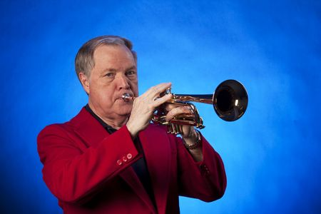 A senior male man playing gold brass trumpet isolated against a blue background. Stock Photo - 5183490