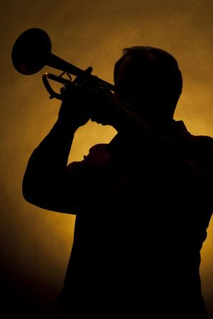 A silhouette of a trumpet being played by a trumpet player in the vertical format with copy space and a gold background. Stock Photo