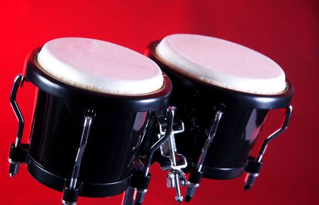 bongos: A set of black bongos isolated against a red background in the horizontal format with copy space.