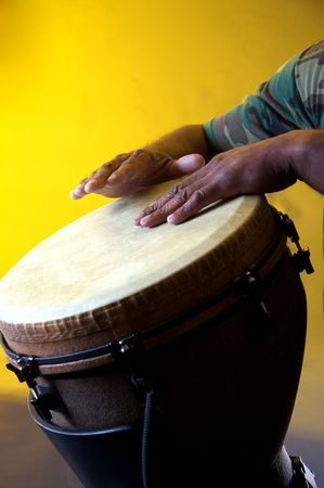 An African or Latin brown djembe conga drum being played against a yellow background in the vertical format with copy space.
