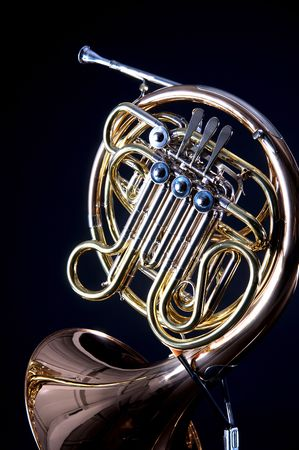 A gold brass French  Horn isolated on a black background in the vertical format with  copy space. Stock Photo