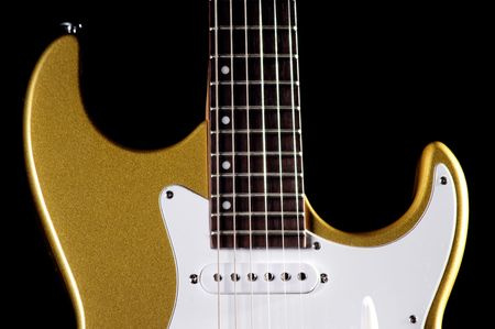 A metallic gold electric guitar isolated on a low key black background in the horizontal format with copy space.