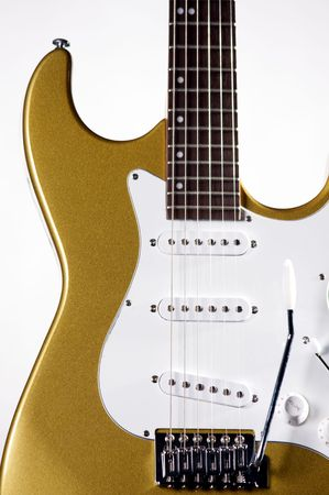A metallic gold colored electric guitar isolated on a white background in the vertical format with copy space.