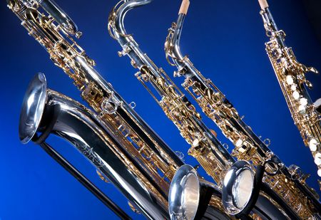 the tenor: A set of four saxophones including a baritone, tenor, alto, and soprano isolated against a blue background in the horizontal format with copy space.