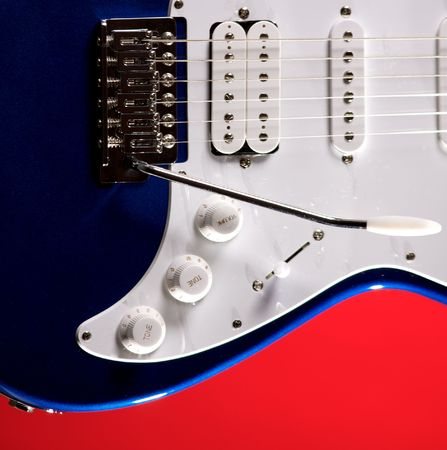 pickups: A metallic blue electric guitar isolated on a red background in the square format with copy space.