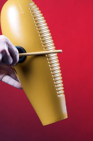 A guiro gourd percussion instrument being played against a red background in the vertical format with copy space. Stock Photo