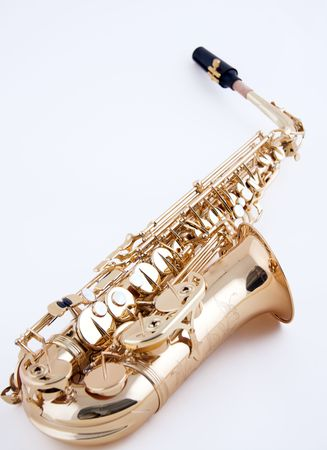 An alto saxophone isolated closeup against a high key white background in the vertical or portrait view with copy space.