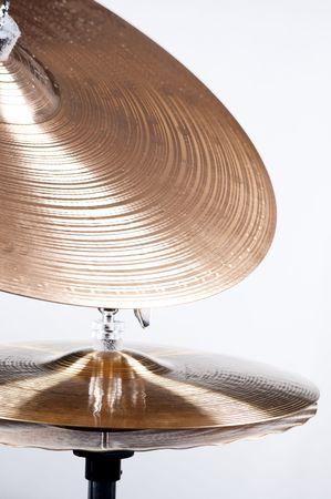 コピー スペースで垂直方向の形式で白い背景に対して隔離されるドラム シンバルのセット。