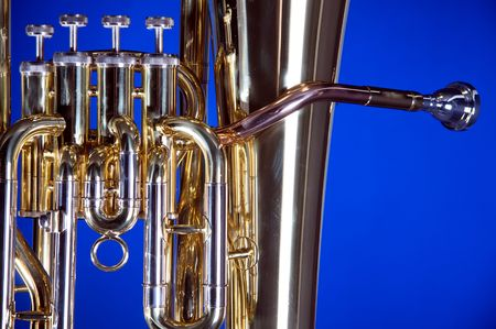 tuba: A gold brass bass tuba euphonium isolated on a blue background in the horizontal format with  copy space.