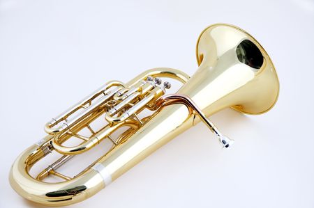 A complete gold brass tuba or euphonium isolated against a high key white background in the horizontal format with  copy space.