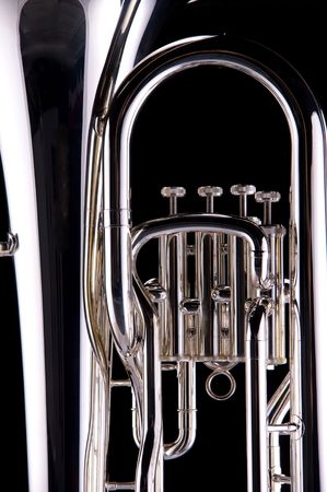tuba: A silver tuba euphonium isolated against a black background in the vertical format.
