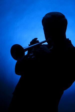コピー スペースで垂直方向の形式で青い背景に対してシルエットでプロのトランペット奏者。