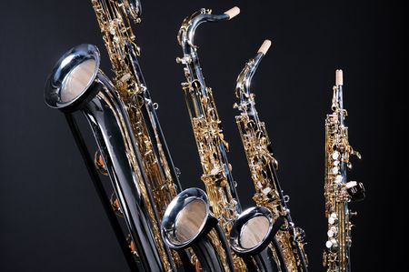A set of four saxophones including soprano, alto, tenor, and baritone isolated against a black background. photo