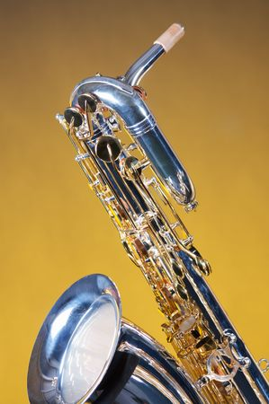A silver and gold baritone saxophone isolated against yellow background. photo
