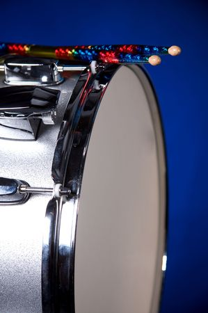 A silver sparkle snare drum with colorful sticks isolated against blue background in vertical format. Stock Photo - 5248222