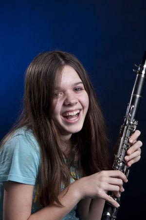 A teenage girl laughing and holding her clarinet music instrument isolated against a blue background in the vertical format. Stock Photo - 5241013