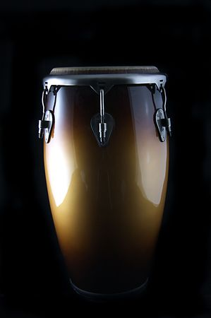 A brown Latin or African conga  drum isolated against a  black background in the vertical format with copy space. Banco de Imagens
