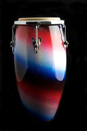 A silver, red, and blue Latin or African conga  drum isolated against a  black background with copy space.