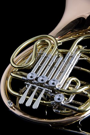 vertical format: A gold brass French Horn isolated against a black background in the vertical format with copy space.