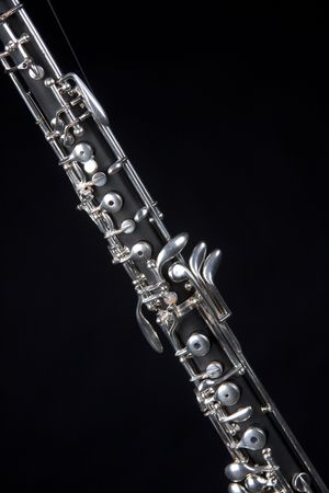 double reed: An oboe up close isolated against a black background in the vertical format with copy space.