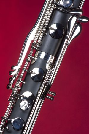 Bass clarinet keys isolated against red background in the vertical format with copy space.