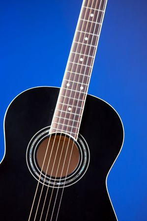A black acoustic guitar isolated against a blue background in the vertical format with copy space. Stock fotó