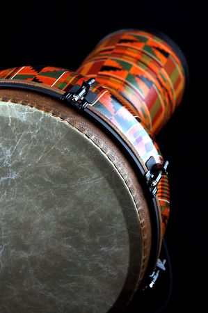 An orange African or Latin Djembe conga drum isolated on black background in the vertical format with copy space. Stock Photo - 5248237