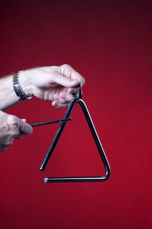 A musical triangles being played by hands isolated against a red background in the vertical format with copy space. Stock Photo - 5248232