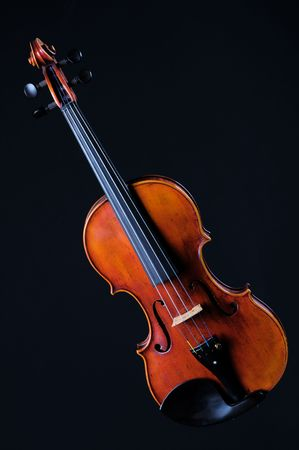 A complete violin viola isolated against a black background in the vertical format with copy space.
