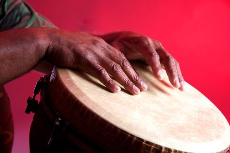 tambor: An African or Latin Djembe being played against a red background in the horizontal format.