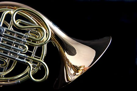 french horn: A brass and copper French horn isolated against a black background in the horizontal format with copy space.