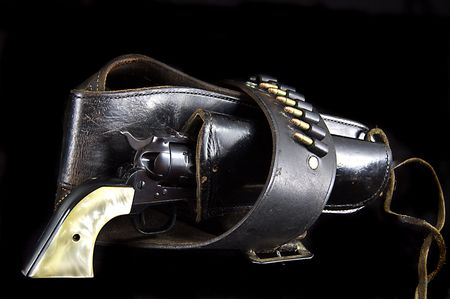 An old western six gun revolver isolated against  a black background in the horizontal format.
