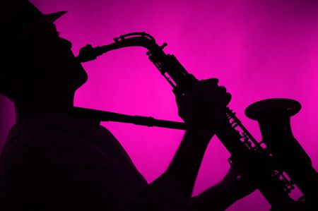 A jazz saxophone being played in silhouette against a low key pink background in the horizontal format.