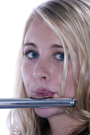 A blond blue eyed teenage female girl playing a silver flute against a white  background  in the  vert photo