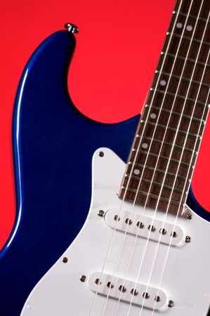 pickups: A blue color electric guitar isolated against a red background in the vertical format with copy space.