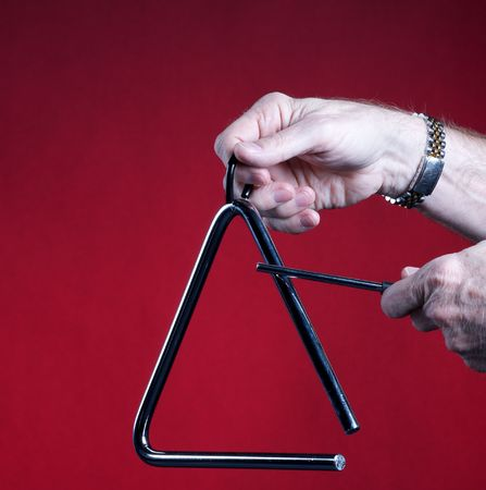 A musical triangle being played by hands isolated against a red background in the square format with copy space. Stock Photo - 5267824