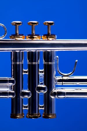 vertical format: Silver trumpet valves with gold trim isolated against a blue background in the vertical format. Stock Photo