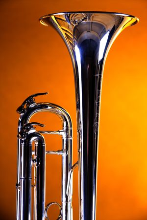 A silver trumpet bell isolated against a gold background spotlight in the vertical format. Banco de Imagens