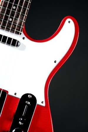 An electric metallic red guitar isolated on a black background in the  vertical format with copy space.