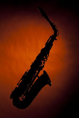 An alto saxophone silhouette isolated against a spotlight gold background in the horizontal view with copy space