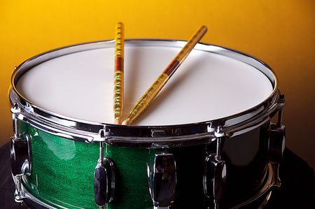 A green snare drum isolated against a gold background in the horizontal format with copy space. Stock Photo - 5549801