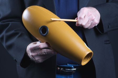 shekere: A guiro gourd percussion instrument being played against a black background in the horizontal format with copy space.