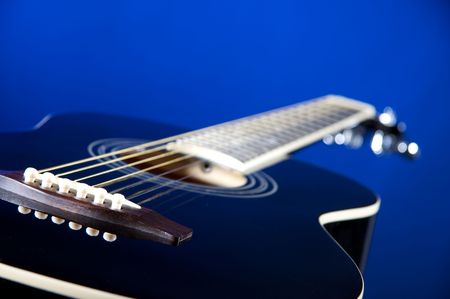 A black acoustic guitar isolated against a blue background in the horizontal format with copy space.