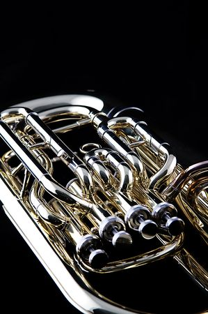 A gold brass tuba euphonium isolated against a black background in the vertical format with copy space. Banco de Imagens