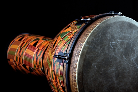 djembe: An orange African or Latin Djembe conga drum isolated on black background in the horizontal format with copy space.