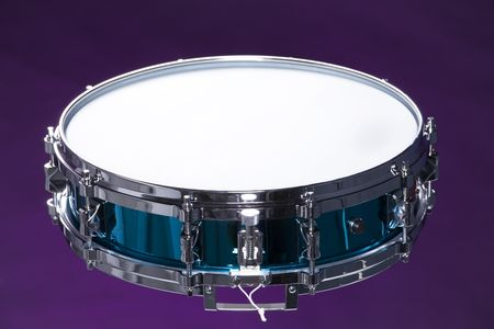 horizontal format horizontal: A metallic blue snare drum isolated against a purple background in the horizontal format.