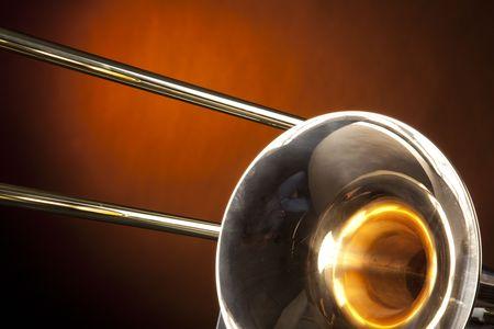 trombón: Un oro de lat�n tromb�n m�sica instrumento de viento aislado contra un foco de oro amarillo en el formato horizontal. Foto de archivo