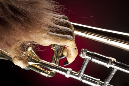 horizontal format horizontal: A Halloween holiday gold brass trombone with a monsters hand against a red and black background in the horizontal format. Stock Photo